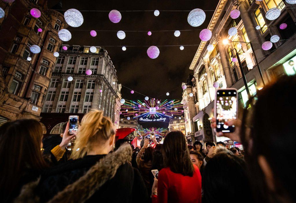 Pedestrians photographing Oxford Street Christmas light show