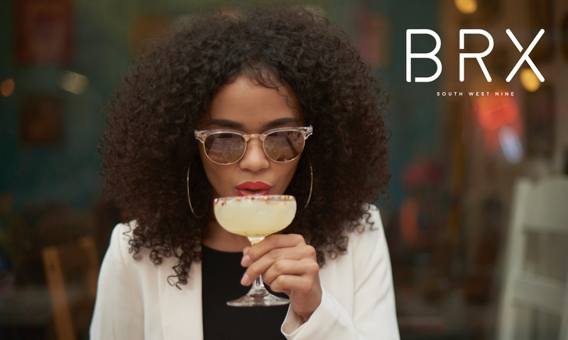 Woman in sunglasses drinking cocktail BRX